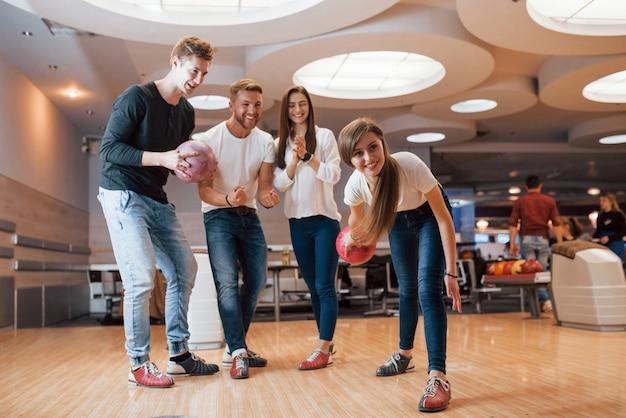 Maak een mooie foto. jonge, vrolijke vrienden vermaken zich in het weekend in de bowlingclub