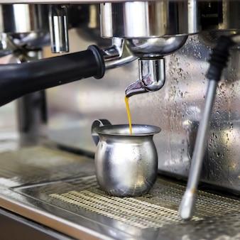 Maak espresso met een koffiemachine. verse koffie gaat van de machine naar de metalen kan