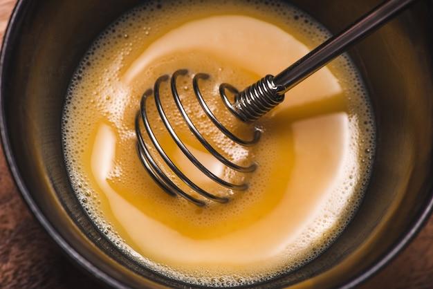 Maak het ontbijt klaar van eieren. slagroom eieren op houten tafel.