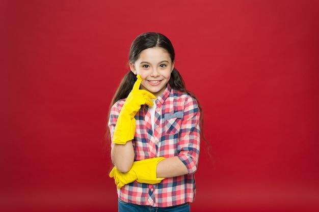 Maak het op een gemakkelijke manier. voorjaars-schoonmaak. huis schoonmaakservice. schoonmaakproducten. kleine meisjes rubberhandschoenen voor het schoonmaken van rode achtergrond. waardeer reinheid. schoon huis. huishoudelijke taken.
