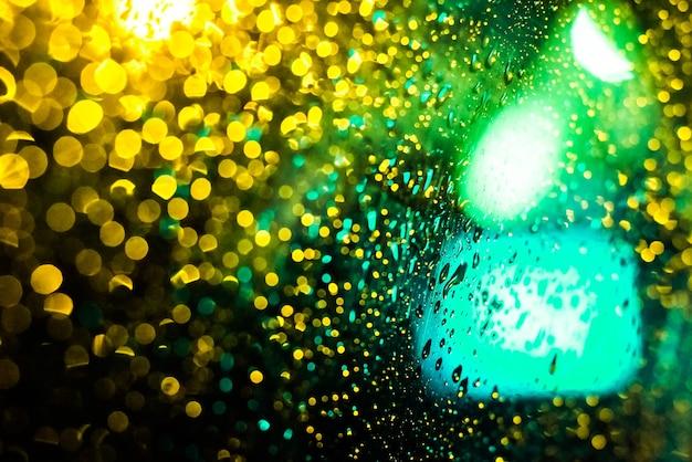 Maak het raam nat met de achtergrond van de herfstnachtstad. geel, groen, aqua, groen tij. onscherp. felle lichten, bokeh.