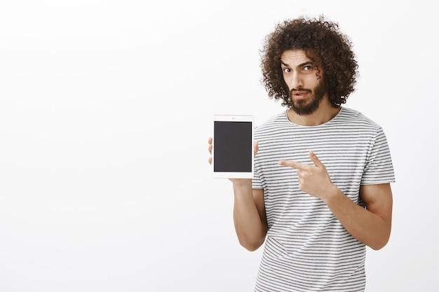 Maak je een grapje. portret van onzekere aarzelende knappe mannelijke collega in gestreept t-shirt, die bezorgd kijkt terwijl hij digitale tablet toont