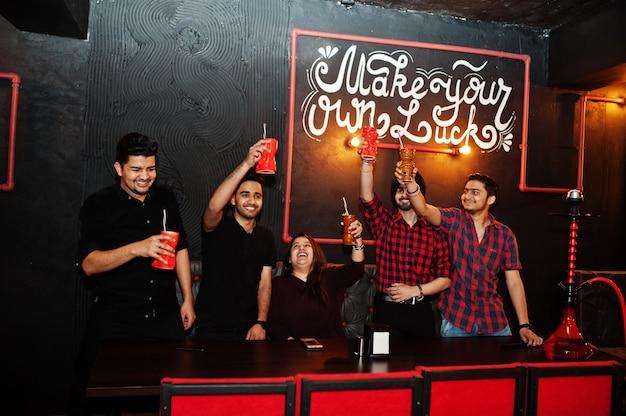 Maak je eigen geluk! groep vrienden met plezier en rust in nachtclub, cocktails drinken, proost en hookah roken