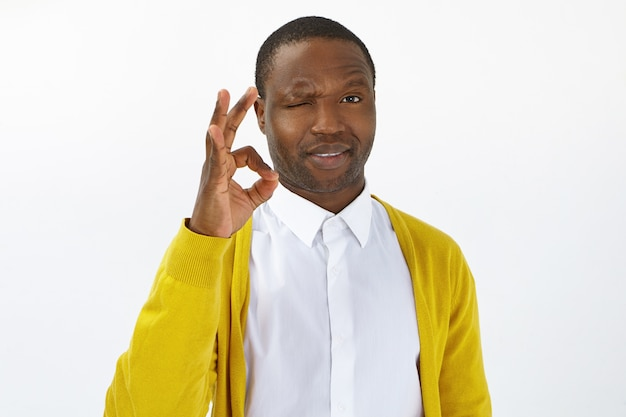 Maak je geen zorgen, alles komt goed. knappe jonge afro-amerikaanse man met borstelharen knipperen naar camera en ok gebaar maken als teken van goedkeuring, zoals en positieve houding, goede emoties uitdrukken