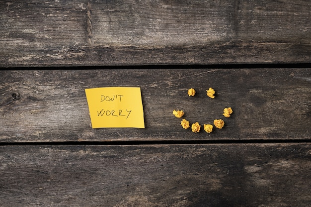 Maak je geen zorgen bericht op een geel post-it-papier met een lachend gezicht gemaakt van kleine gekreukte papieren