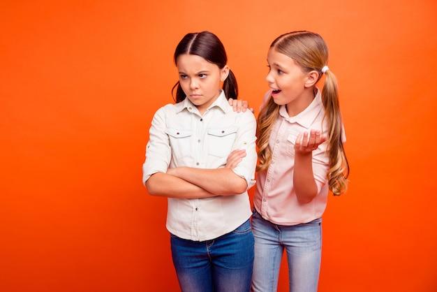 Maak je geen zorgen, relax blond haar kind vriendin ondersteuning latijns schoolmeisje kruis handen frons gezicht gevoel woede emoties oneens met familie klasgenoten dragen wit overhemd geïsoleerde oranje kleur achtergrond