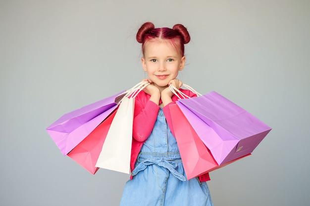 Maak kennis met de kortingen. gelukkig klein babymeisje glimlacht met papieren boodschappentassen.