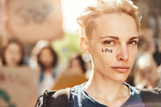Maak liefde geen oorlog close-up foto van jonge blonde vrouw met woord liefde geschreven