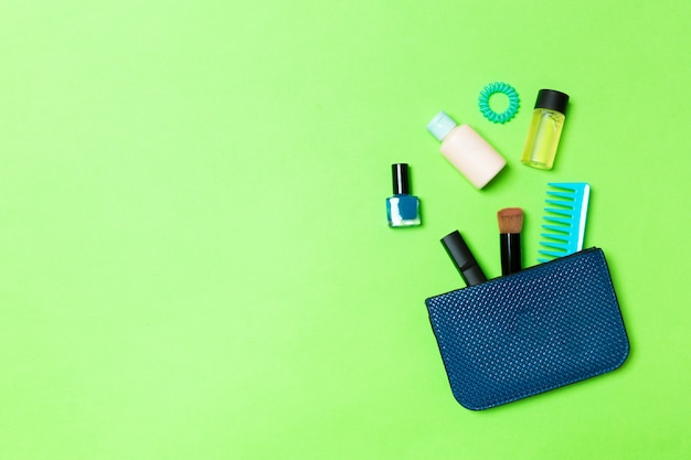 Maak omhoog producten die uit schoonheidsmiddelenzak op groene achtergrond morsen