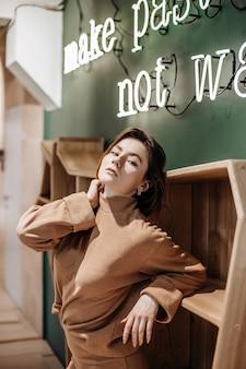 Maak pasta, geen oorlog. stijlvol jong mooi meisje met rood haar staat in de buurt van het meubilair tegen een groene muur binnenshuis in warme kleding met een stijlvol interieur. toegang tot het restaurant