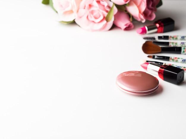 Maak producten lippenstift, bloos en hulpmiddelenborstels met roze rozenbloemen op witte achtergrond. levensstijl vrouw stilleven
