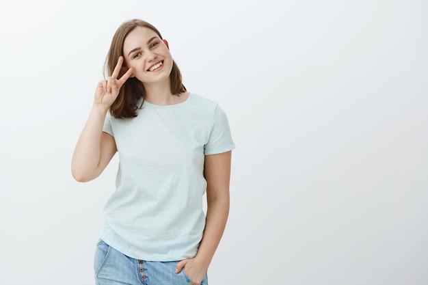 Maak vrede, vecht niet. portret van gelukkig charmant europees meisje met bruin haar in vrijetijdskleding hand in de zak met overwinningsteken in de buurt van gezicht kantelen hoofd en glimlachend vredig en vreugdevol