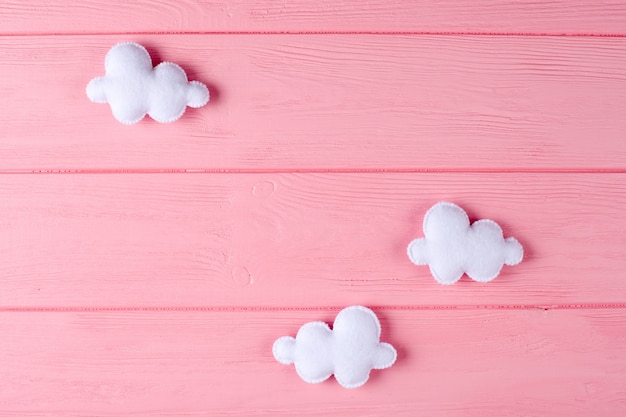 Maak witte wolken met kader, copyspace op roze houten achtergrond tot een kom. met de hand gemaakt viltspeelgoed.