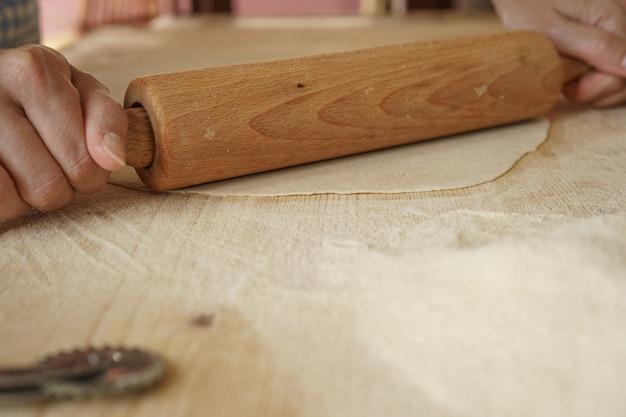 Maakproces van zelfgemaakte veganistische farfalle pasta. de kok gebruikt een deegroller om het deeg uit te rekken