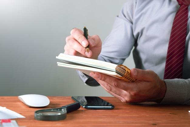Maakt aantekeningen in een notitieboekje.