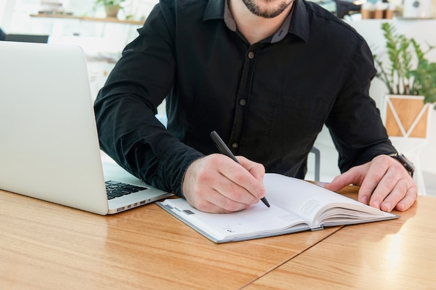 Maakt afsprakennotities, schrijft belangrijke dingen en to-do lijst. geconcentreerde man zit aan het bureau, houdt een pen vast, houdt zakelijke ideeën voor opstarten, plannen, creatieve gedachten vast aan een close-up beeld van een notebook.