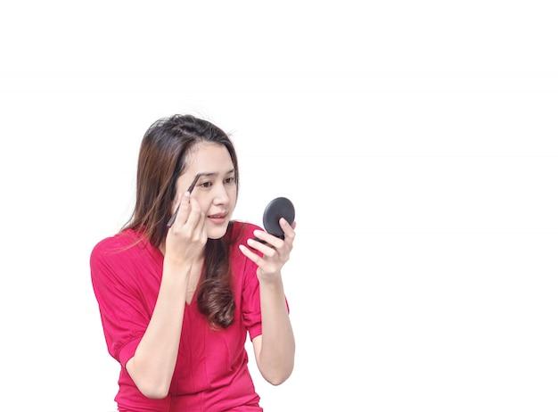 Maakt de aziatische vrouw van de close-up omhoog wenkbrauw met wenkbrauwpotlood dat op witte achtergrond in kosmetisch concept wordt geïsoleerd