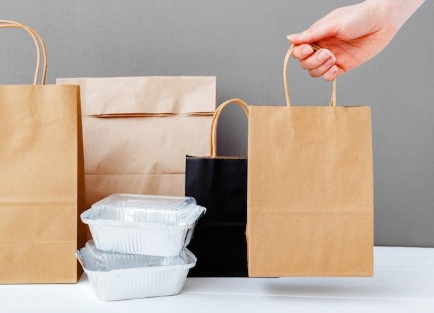 Maaltijdbezorging. bruine ambachtelijke papieren zak verpakking in vrouwelijke hand. levering verpakking. de foliecontainers van het voedsel en document pakketten op lijst grijze achtergrond. afhaalmaaltijden.