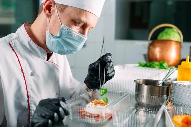 Maaltijdbezorging in het restaurant. de chef-kok bereidt eten in het restaurant en verpakt het in wegwerpschalen.