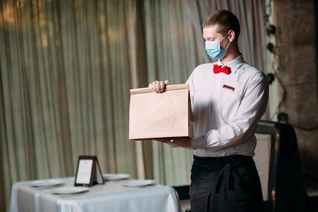 Maaltijdbezorging vanuit het restaurant. portret van een ober die een ambachtelijke papieren zak voor de levering van voedsel.