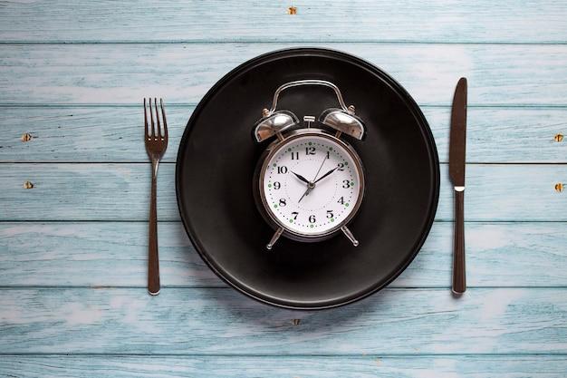 Maaltijdplanning voor dieetconcept, intermitterend vastenconcept met klok op plaat, vork en mes op houten lijst