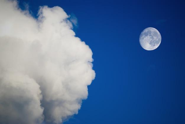Maan en wolken aan de blauwe hemel