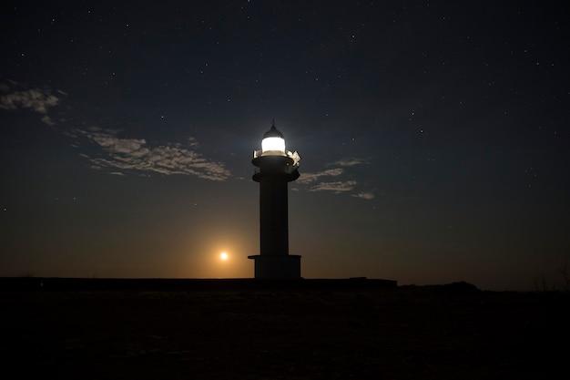Maan gluurt 's nachts achter een vuurtoren vandaan