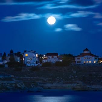 Maan over de rivier bij de stad met blauwe lucht en wolken