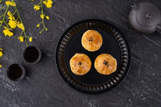 Maancake dooiergebak, mooncake voor mid-autumn festival-vakantie, bovenaanzicht ontwerpconcept op donkere houten tafel met kopie ruimte, plat leggen, overhead schot