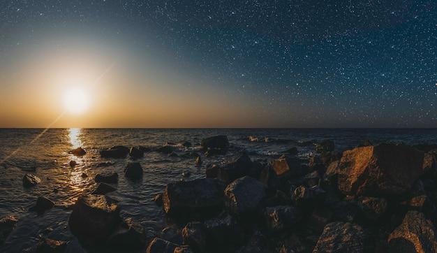 Maand op een achtergrond sterrenhemel weerspiegeld in de zee.