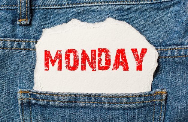 Maandag op wit papier in de zak van blauwe spijkerbroek