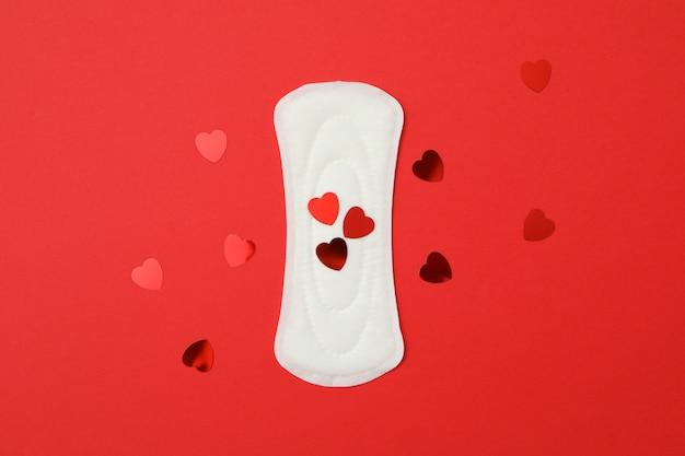 Maandverband en kleine hartjes op rood oppervlak