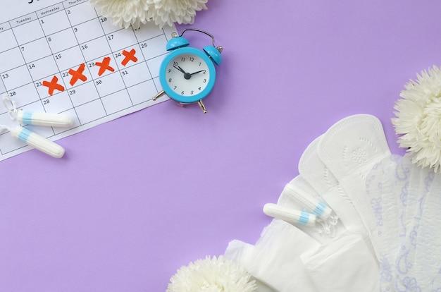 Maandverband en tampons op menstruatie kalender met blauwe wekker en witte bloemen