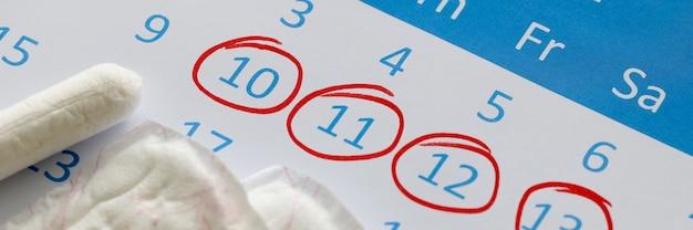 Maandverband en tampons staan op de kalender. getallen zijn omcirkeld in rode pen. vrouwelijke menstruatiecyclus concept