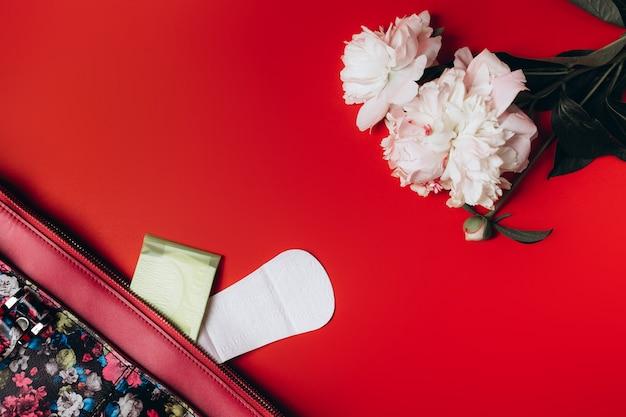 Maandverband steekt uit de tas en in de hoek staan prachtige pioenen