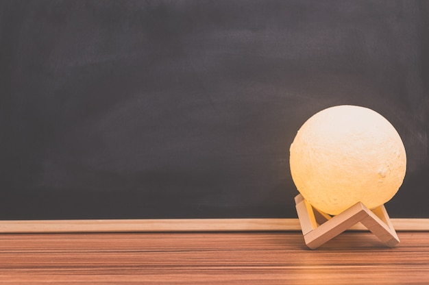 Maanvormlamp op het bureau blackboard background