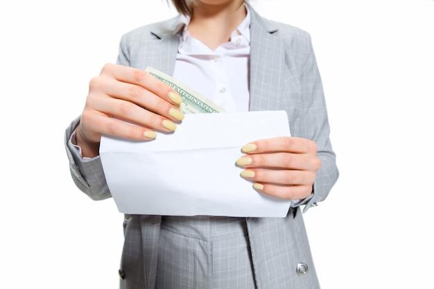 Maar waar is het geld. jonge vrouw in grijs pak krijgt een klein salaris en gelooft haar ogen niet. geschokt en verontwaardigd. concept van de problemen, zaken, problemen en stress van de kantoormedewerker.