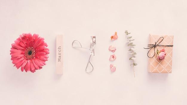 Maart-inscriptie met bloemen en geschenkdoos op tafel
