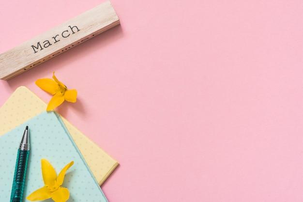 Maart-inscriptie met gele bloemen en notitieblokken