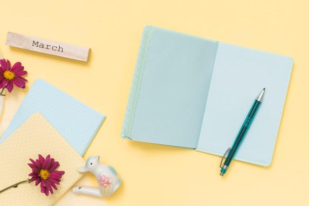 Maart-inscriptie met notitieboekje en bloemen