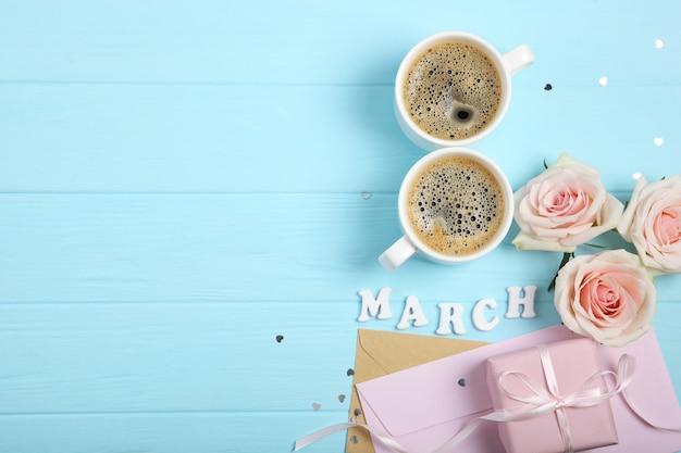 Maart tekst met kopjes koffie en roze cadeau en bloemen op blauwe achtergrond