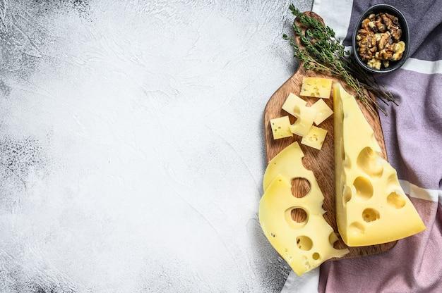 Maasdammer kaas met gaten, melkgele driehoek. grijze achtergrond