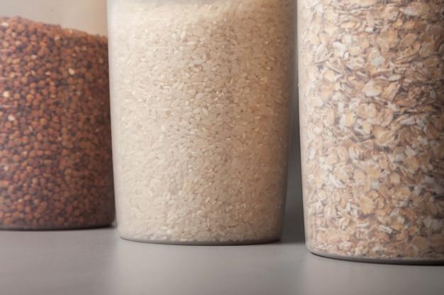 Maatblikken van 1000 en 400 kubieke maat voor het opslaan van bulkproducten met voedsel op grijze achtergrond. transparante plastic container voor het bewaren van voedsel en bulkproducten. granen en bulkproducten in potten