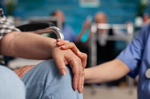 Maatschappelijk assistent die gehandicapte gepensioneerde patiënt troostende handen aanraakt