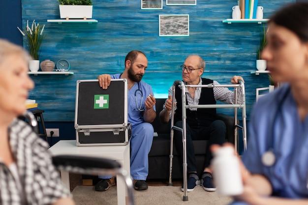 Maatschappelijk assistent die medicijnen voor de gezondheidszorg bespreekt met bejaarde gehandicapte gepensioneerde