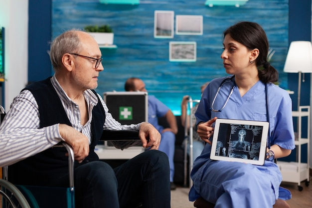 Maatschappelijk verpleegkundige die medische radiografie met behulp van tabletcomputer uitlegt aan gepensioneerde gehandicapte senior man patiënt. sociale diensten verpleging bejaarde gepensioneerde man. hulp in de gezondheidszorg