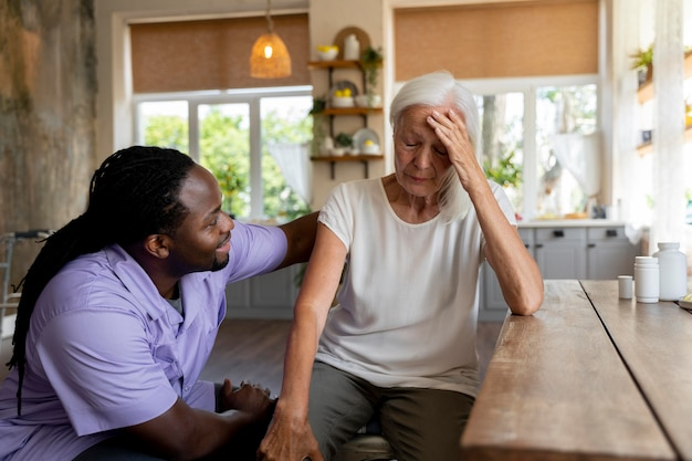Maatschappelijk werker die een oudere vrouw helpt