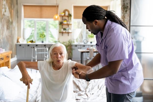 Maatschappelijk werker die voor een oude vrouw zorgt