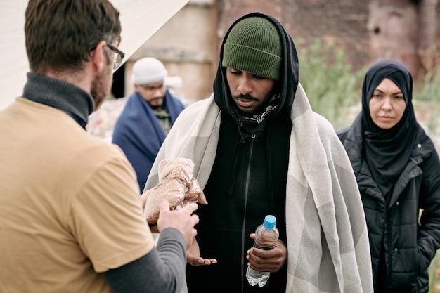 Maatschappelijk werker die water en ontbijtgranen geeft aan zwarte man onder plaid terwijl hij buitenshuis voedsel aan vluchtelingen geeft