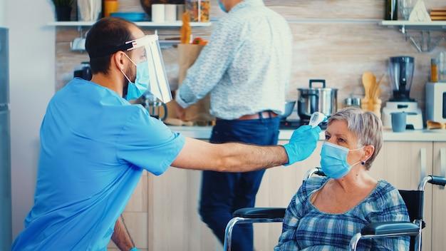 Maatschappelijk werker met gezichtsmasker die lichaamstemperatuur van gehandicapte senior vrouw in rolstoel neemt tijdens huisbezoek en coronavirus pandemie. geriater helpt verspreiding van covid-19 te voorkomen